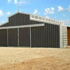 Barn with sliding doors, poly carbonite sidelights, weather vane and open access to paddocks.